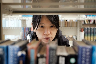 Portrait of serious Asian girl in library looking for a book