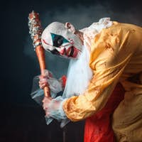 Bloody clown with crazy eyes holds baseball bat