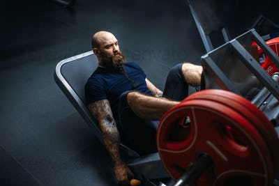 Strong athlete on exercise machine with barbell