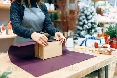 Female seller holds unwrapped carton gift box