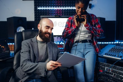 Male sound producer and female singer in studio