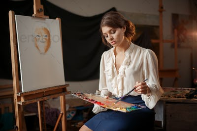 Female painter holds color palette and brush
