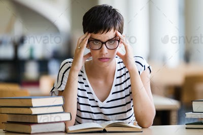 Young stressed student girl studying pile of books