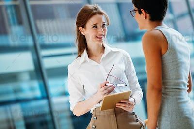 Portrait of two young attractive businesswomen talking on break