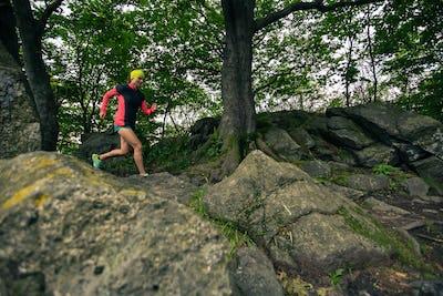Trail running girl in green forest. Endurance sport.