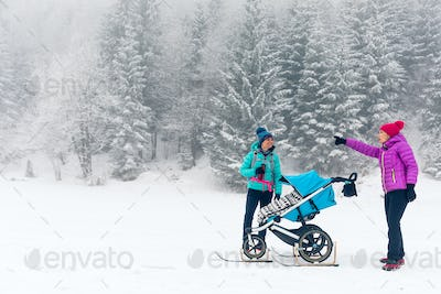 Mother with baby stroller enjoying winter in forest, family time