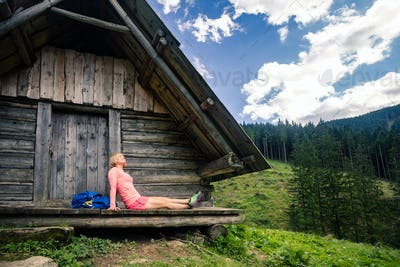 Woman camping and looking at inspiring mountain landscape