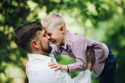 Handsome father throwing baby boy against summer park