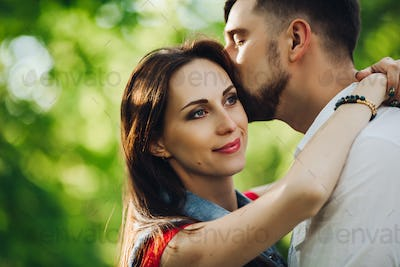 Romantic couple in love, smiling and embracing in garden face to face