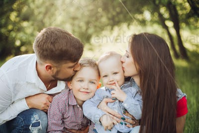 Portrait of young happy family kissing his little son