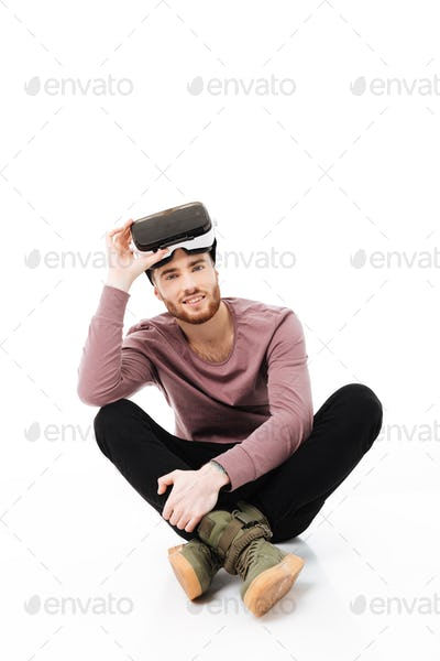 Man sitting in studio and happily looking in camera with virtual reality glasses on head isolated