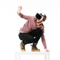 Afraid man standing on white table and take cover of something playing with virtual reality glasses