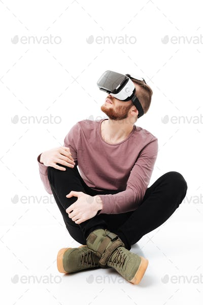 Young man sitting in studio and using virtual reality glasses over white background