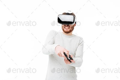 Portrait of young man using virtual reality glasses and playing video game over white background