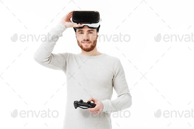 Young man happily looking in camera with virtual reality glasses on his head and joystick in hand