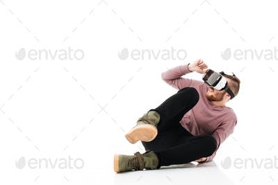 Young man sitting in studio and take cover of something while playing with virtual reality glasses