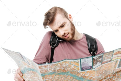 Young man talking on his mobile phone while holding open map in hands on white background