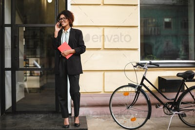 Lady with dark curly hair in suit standing with bicycle and notebook in hand