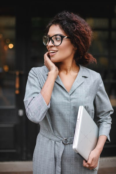 Cheerful African American girl in glasses standing with laptop in hand and emotionally looking aside