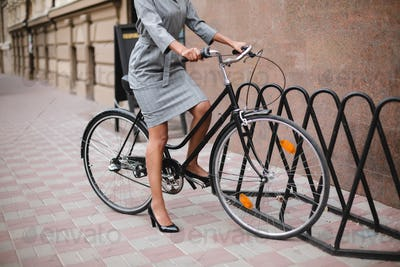 Close up photo of woman body in gray dress standing with bicycle