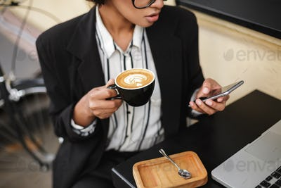 African American girl sitting at the table of cafe with cellphone and cup of coffee in hands