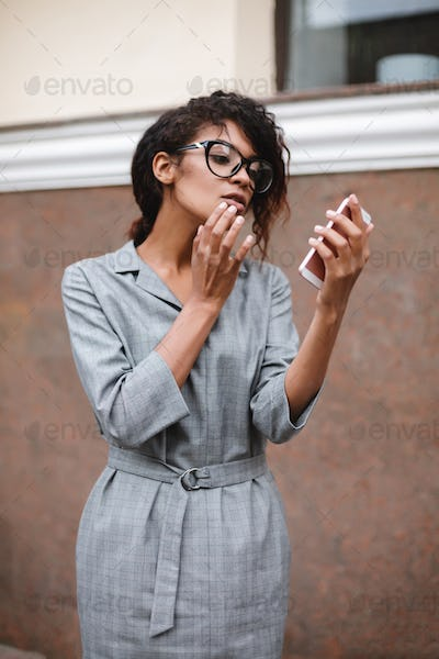 Young beautiful lady with dark curly hair standing and thoughtfully looking in her mobile phone