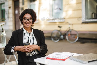 African American girl in glasses sitting at the table and happily looking in camera with coffee