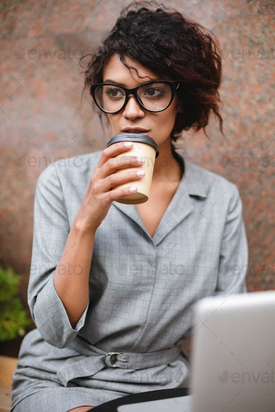African American girl in glasses sitting on bench and drinking coffee while dreamily looking aside