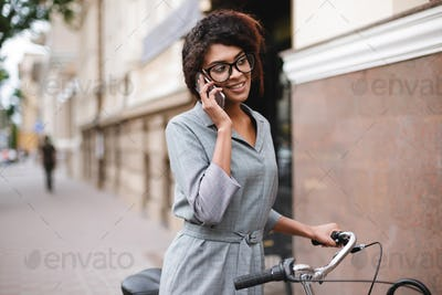 Cheerful African American girl in glasses standing with bicycle and talking on her cellphone