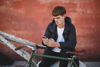 Young man in down jacket and white t-shirt sitting with mobile phone in hands and bicycle nearby