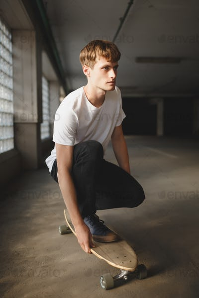 Young thoughtful man in white t-shirt riding on skateboard