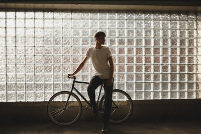 Cool boy standing with classic bicycle and dreamily looking aside while posing on camera