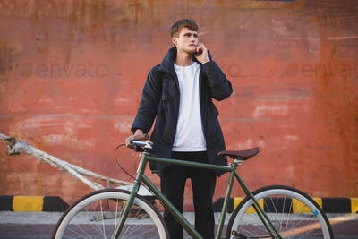 Boy with brown hair standing with classic bicycle thoughtfully looking aside talking on cellphone