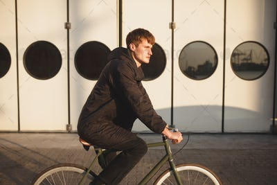 Portrait of young man with brown hair riding classic bicycle and dreamily looking aside