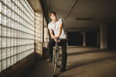 Young thoughtful man in white t-shirt standing with bicycle and mobile phone in hand