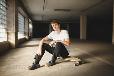 Cool boy with brown hair sitting on skateboard and dreamily looking in camera while smoking