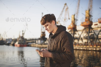 Portrait of young man with brown hair standing and thoughtfully looking in his mobile phone