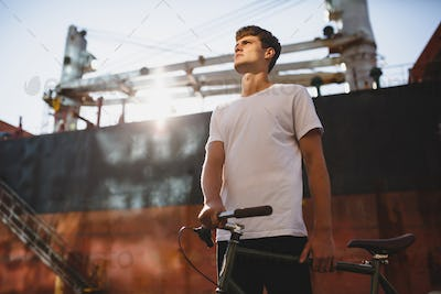 Portrait of serious boy with brown hair standing with bicycle and dreamily looking aside