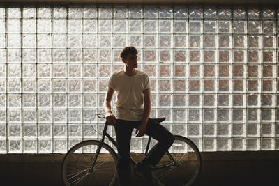 Pensive boy standing with classic bicycle and thoughtfully looking aside while posing on camera