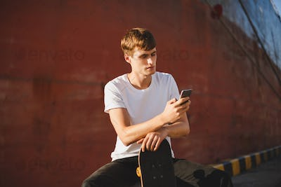 Boy with brown hair sitting with skateboard in hand and thoughtfully looking in cellphone