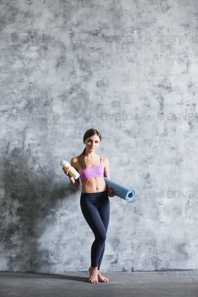 Young beautiful woman after workout with a bottle and yoga mat.