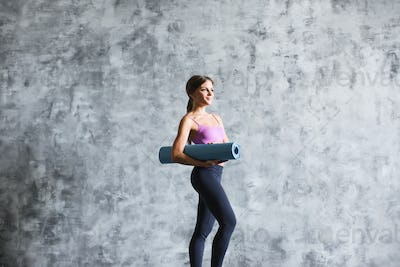 Exercise fitness woman ready for workout standing holding yoga mat.