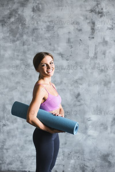 Young beautiful sporty woman with yoga mat.