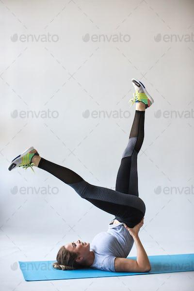 Beautiful woman in sportswear doing stretching on yoga mat.