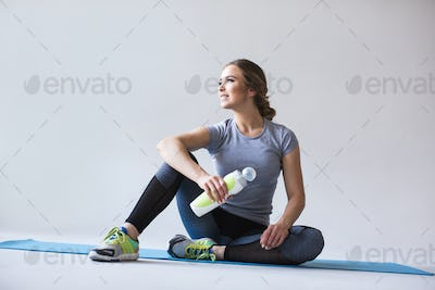 Beautiful smiling woman looking away while sitting on exercise mat at gym.