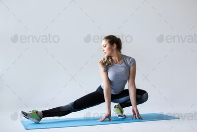 Fitness woman stretching on gray background.
