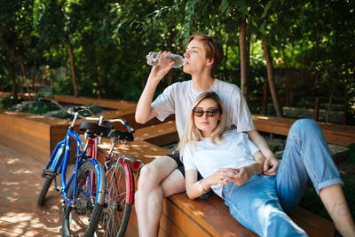 Young couple spending time on wood bench in park with two bicycles nearby