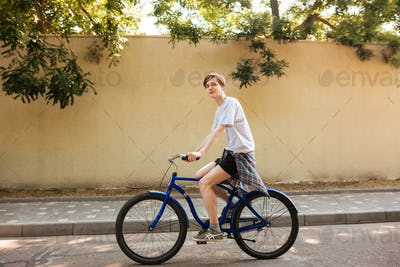 Portrait of smiling boy dreamily looking in camera while riding bicycle
