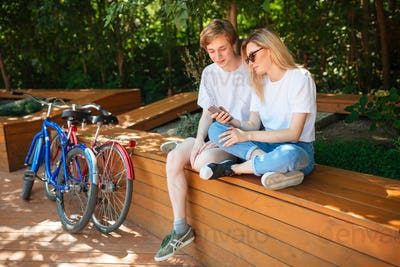 Portrait of cute couple sitting on bench in park and using cellphone