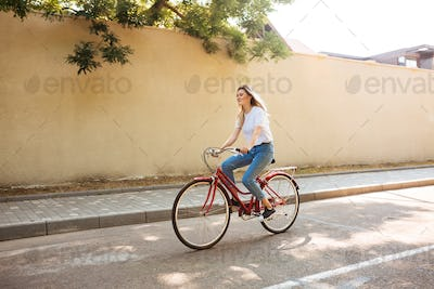 Portrait of young lady in jeans having fun while riding on red bicycle along city streets